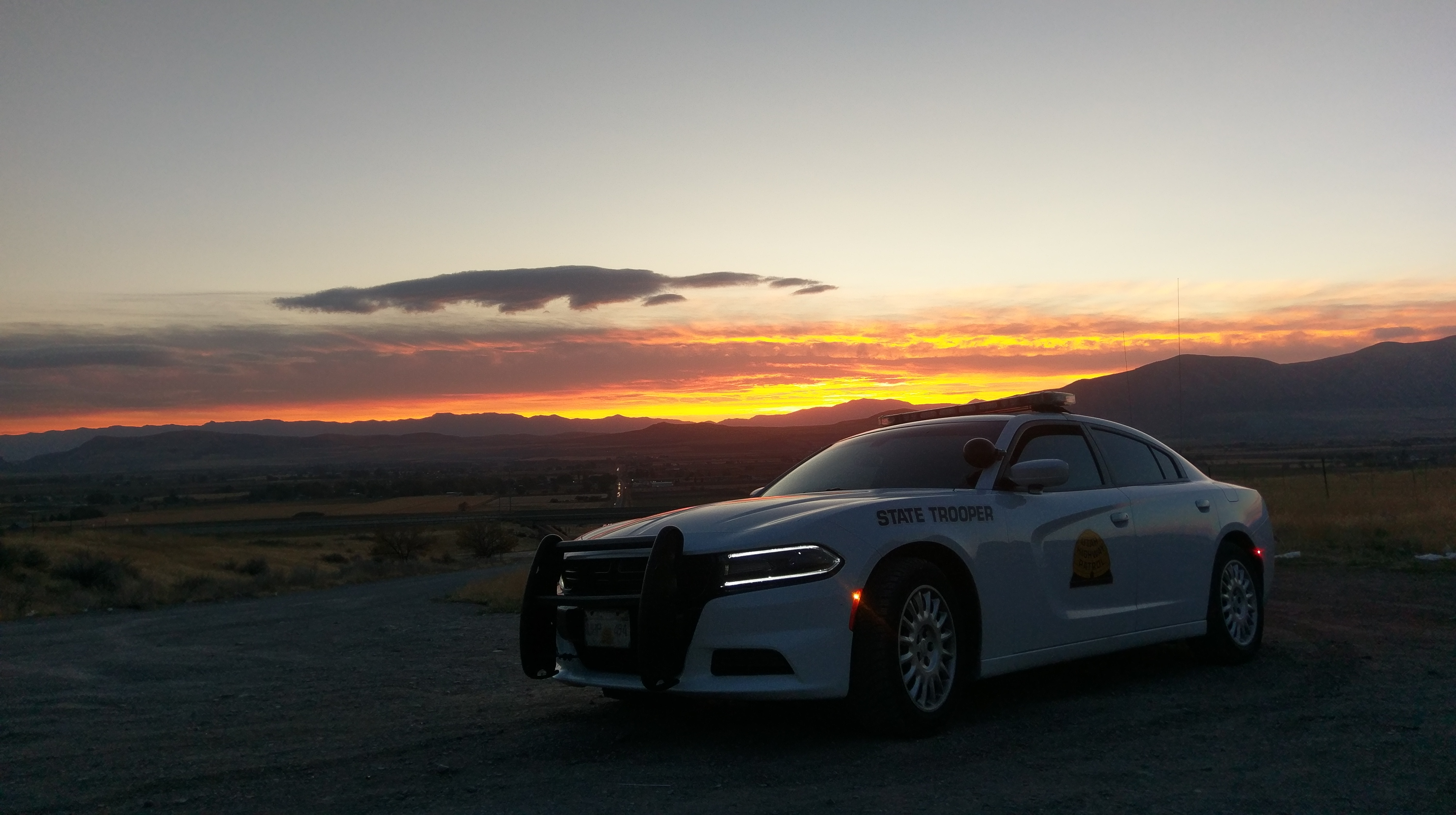 A UHP Dodge Charger with sunset and mountains in the background.