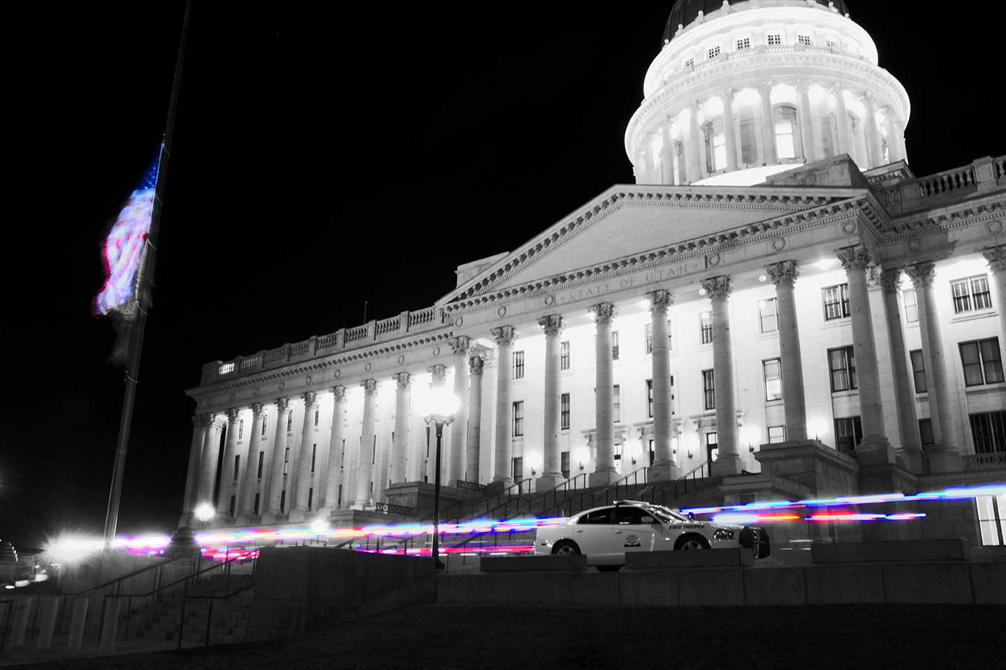 Night time view of the state capitol with trooper cars out front.