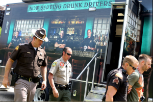 UHP troopers walk in front of the BAT mobile, which is wrapped with a message about drunk driving.