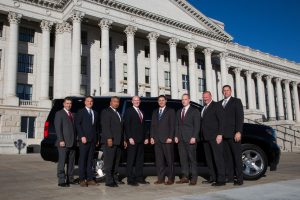 Members of UHP's executive protection team pose in front of a vehicle in front of the state capitol building.