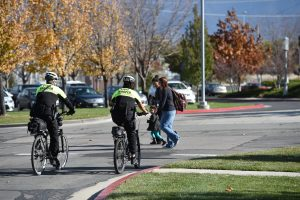 Two troopers assigned to policing at the Salt Lake Community College ride their bikes through the parking lot