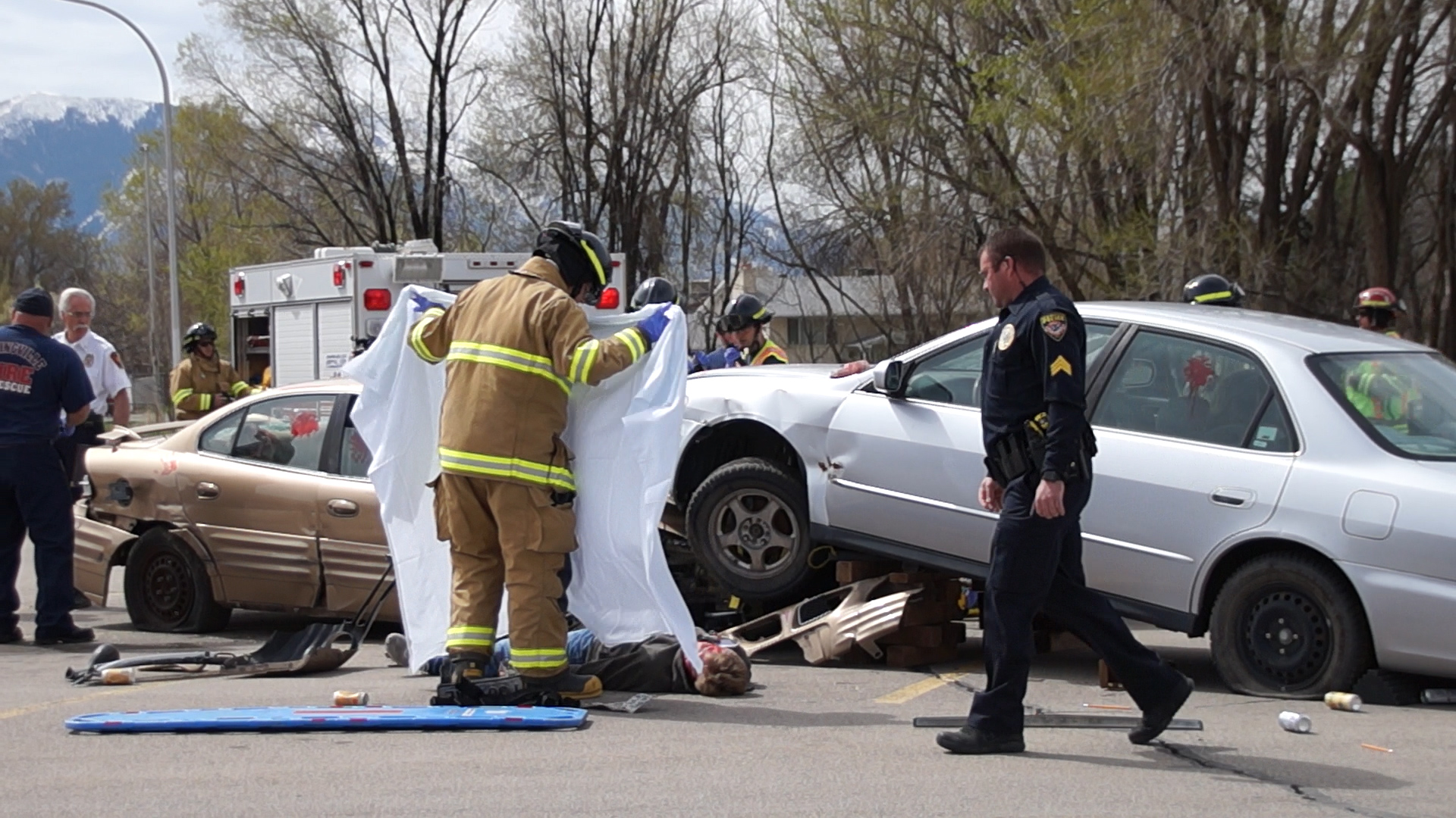EMT prepares to cover dead body with sheet in mock crash. UHP, Springville PD, SPringville Fire and Rescue, Utah County Sheriff's Office and Lifeflight teamed up to conduct a mock crash at Springville High School on April 10th.