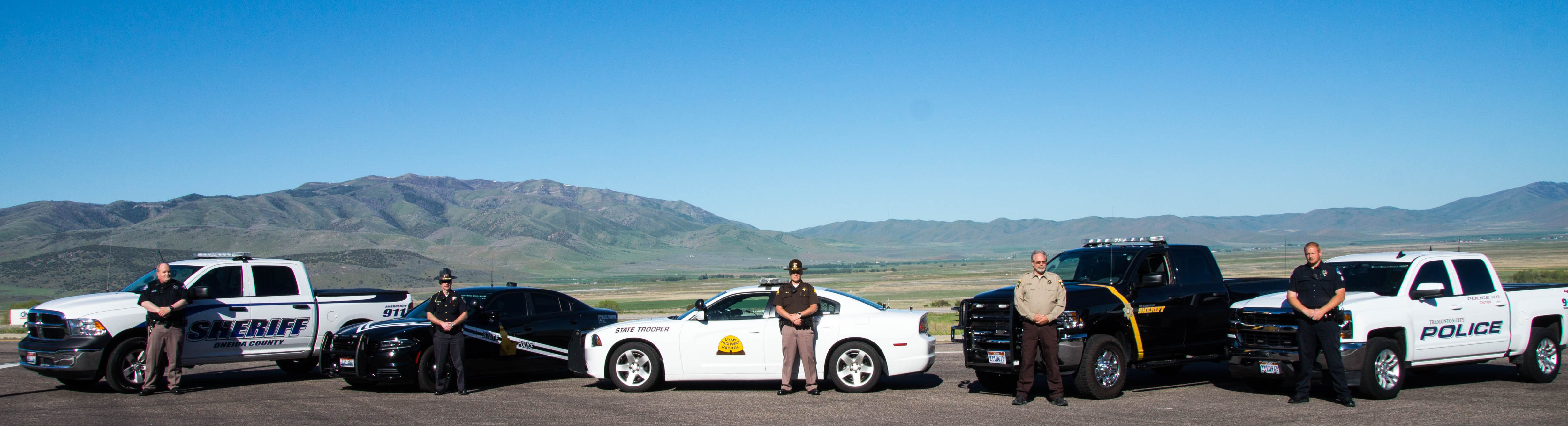 Officers from Oneida County Sheriff's Office, Idaho State Police, Utah Highway Patrol, Box Elder County SHeriff's Office and Tremonton Police Department stand by their vehicles.