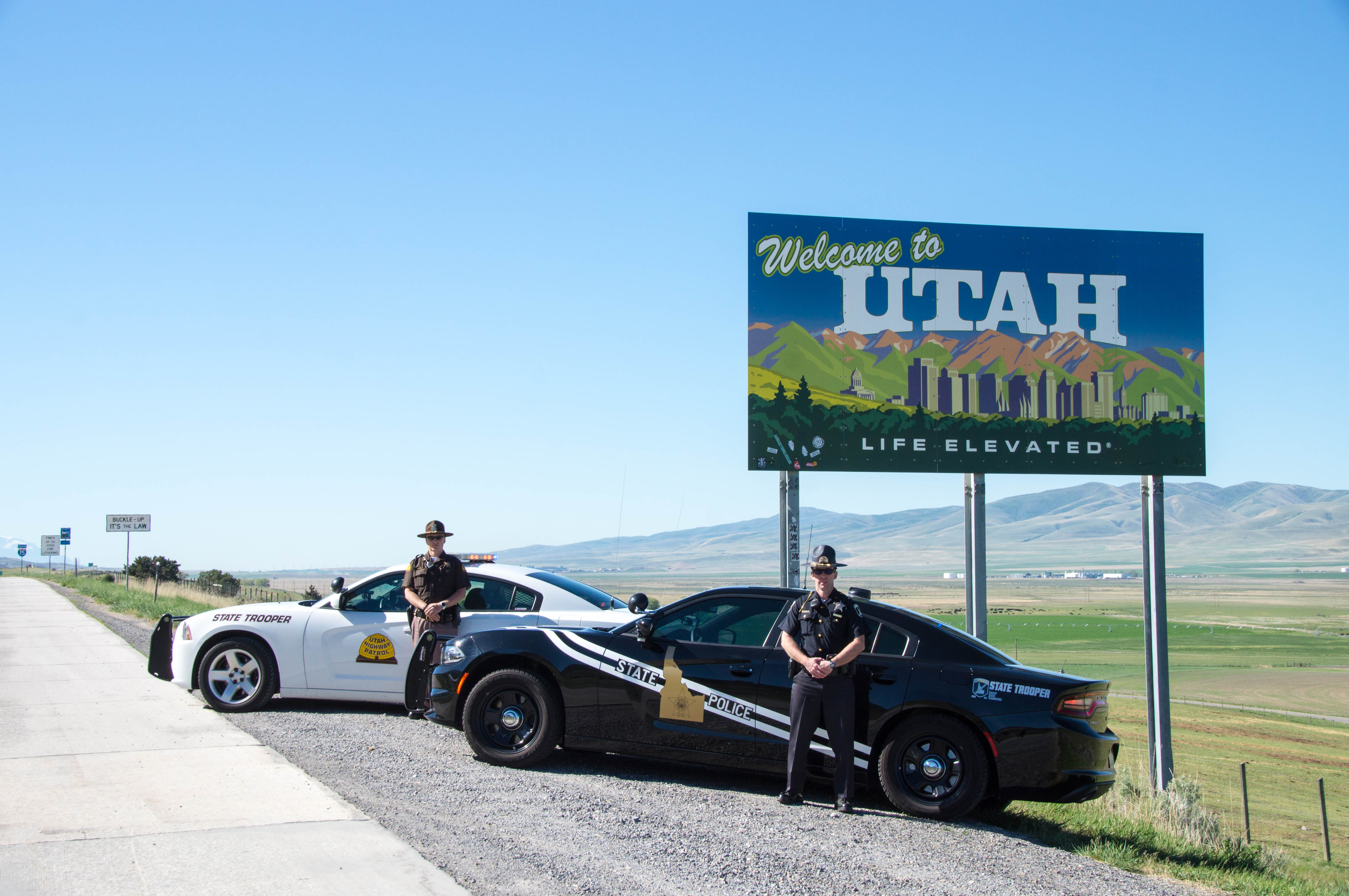 "A UHP Trooper and ISP Trooper stand by their vehicles at the ""Welcome to Utah"" Sign"