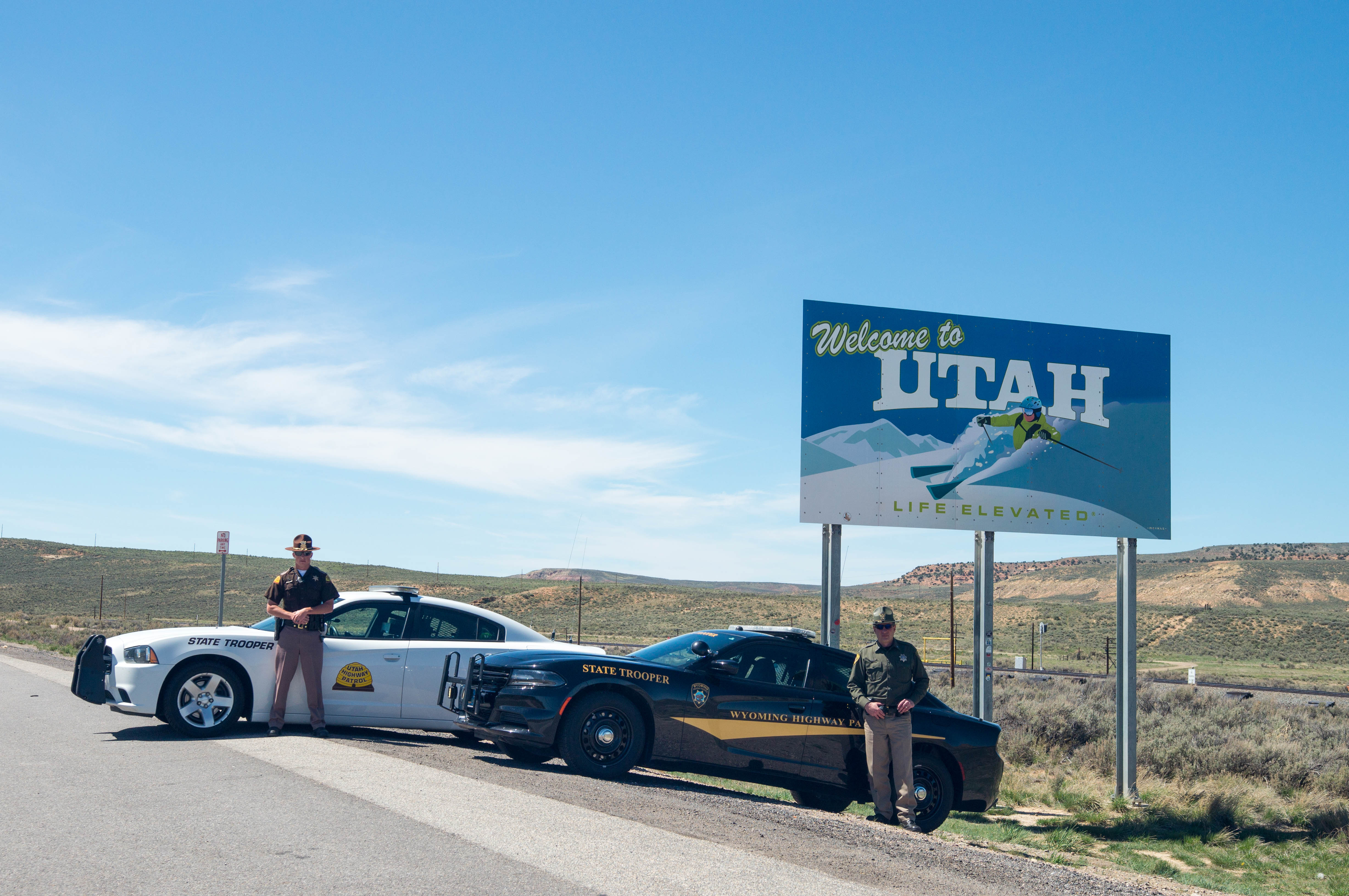 UHP Trooper and WHP Trooper by the welcome to Utah sign outside of Evanston