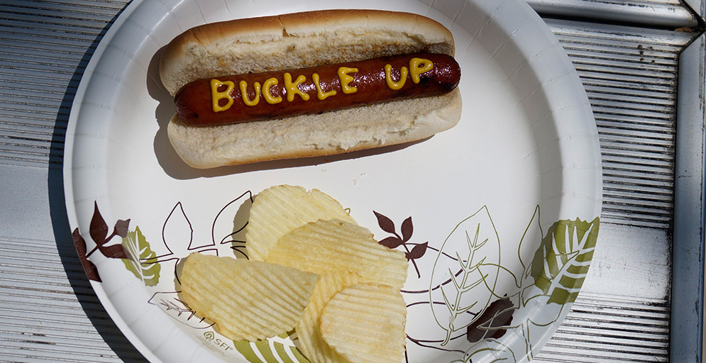 Hot dog with buckle up written in mustard on it.