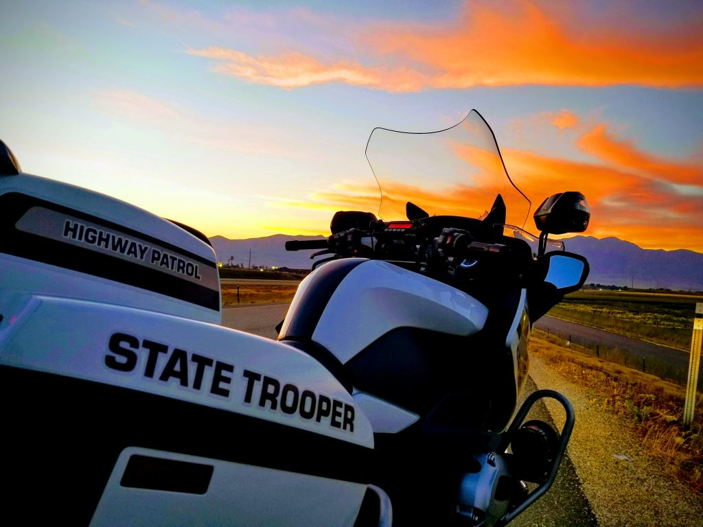 A UHP motor sits on the road shoulder with a Utah sunset lighting the sky. UHP troopers will work an additional 341 extra shifts over the Labor Day weekend