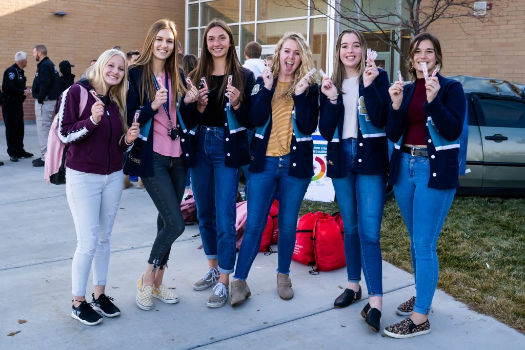 Five students stand on the west side of Salem Hills High School and hold up candy canes.