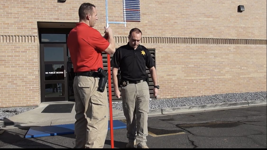 Image shows one UHP trooper standing by a pole used to measure vertical jump height and another trooper preparing to demonstrate how to do the vertical jump.