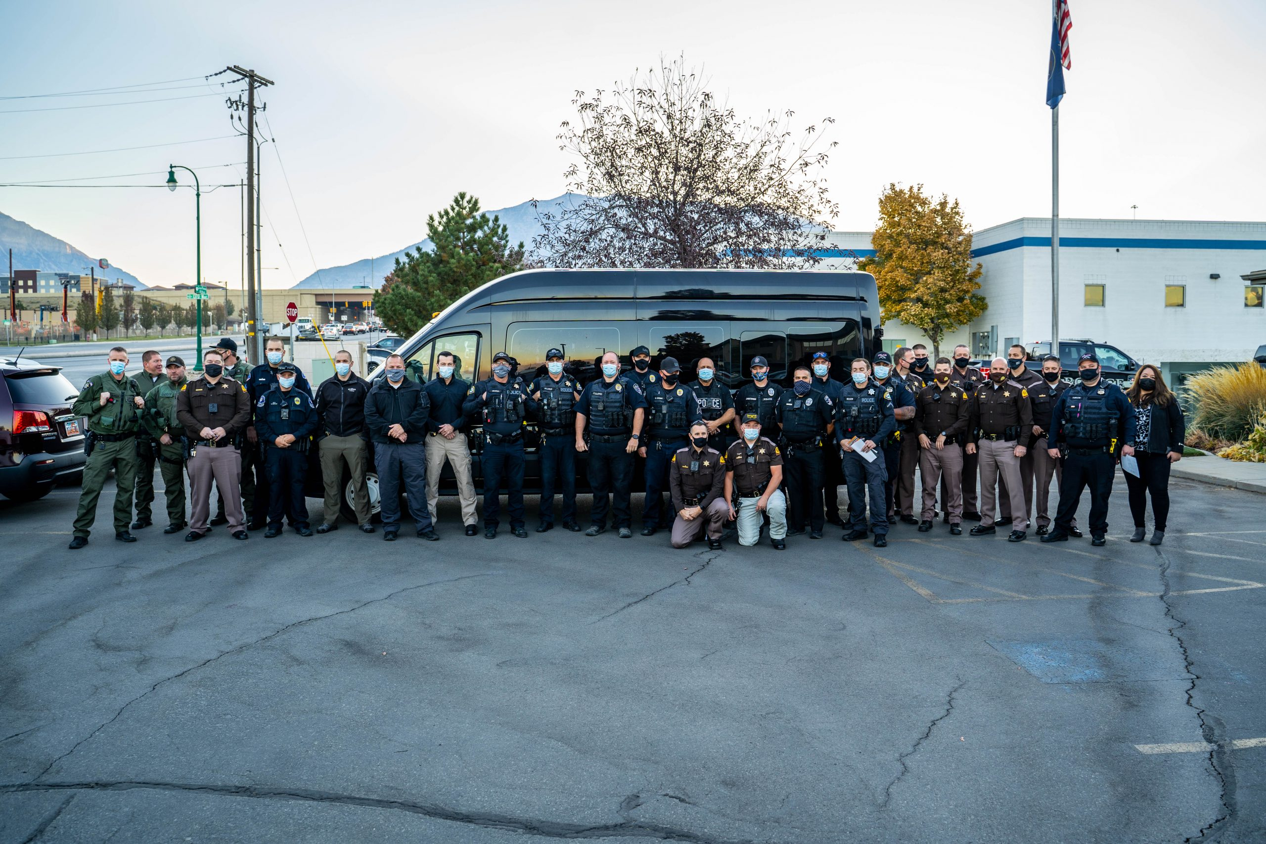 Image shows 32 officers from 7 different police departments standing in front of an unmarked van that will be used for the distracted driving operation.