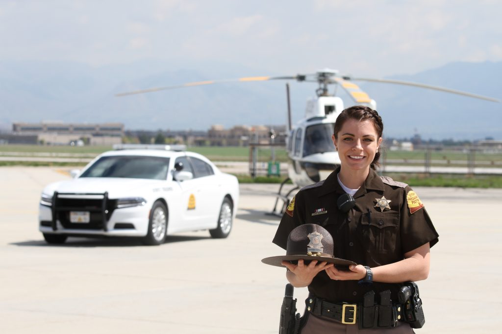 Image shows Trooper Tara Wahlberg standing with a UHP patrol car and UHP helicopter in the background.